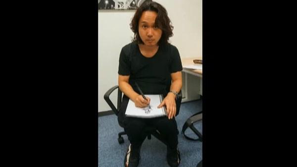 膝の上で描く新川洋司氏