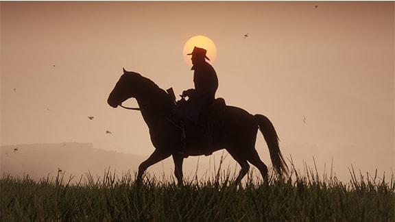Red Dead Redemption2で夕日をバックにガンマンが乗馬している風景